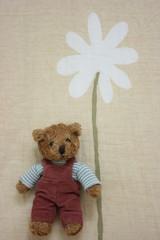 Toy bear holding flower