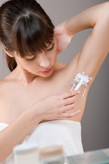 Body care: Woman shaving armpit with razor