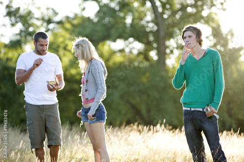 Three young friends standing in a field
