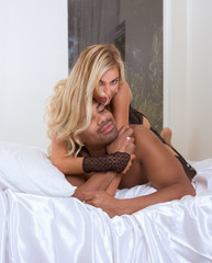 young interracial couple in sexual games on bed