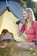 Two young women camping, one drinking a bottle of beer