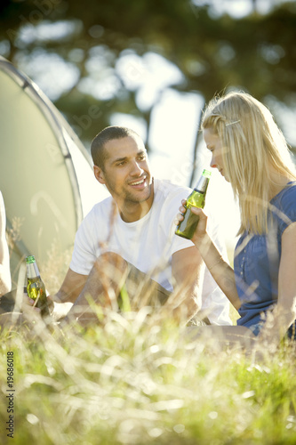 A young couple sitting in front of a tent, drinking beer