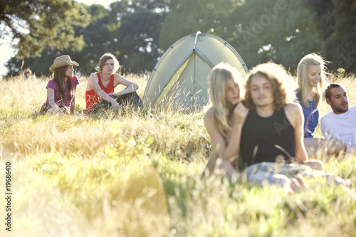 Three young couples sitting in a field near a tent