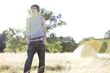 A young man standing in a field near a tent