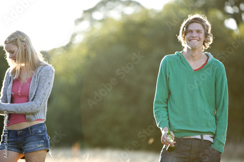 Two young friends standing in a field, one smoking