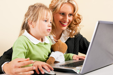 Busineswoman and mother showing kid the internet