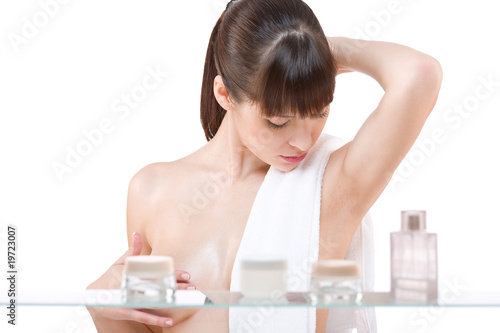 Body care: Young woman applying lotion in bathroom