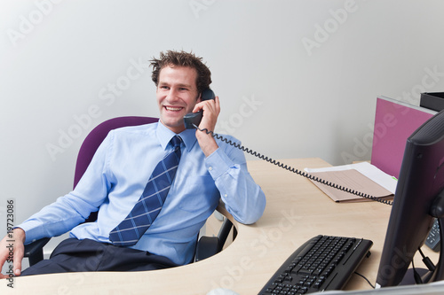 Businessman sat at his desk talking on the telephone.