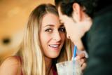 Paar im Restaurant trinkt Michshake poster