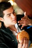 Mann im Restaurant isst Hamburger poster