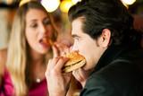 Paar im Restaurant isst Fast-Food poster