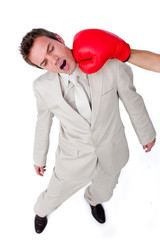 Attractive businessman being hit with a boxing glove