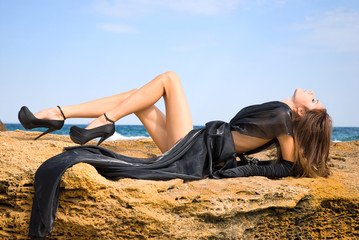Beautiful glamour young girl at the beach in black