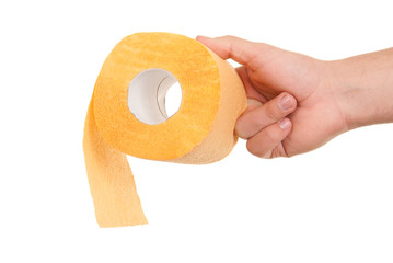 Hand holds roll of yellow toilet paper