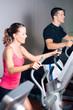 Leute trainieren auf Crosstrainer im Fitnessstudio