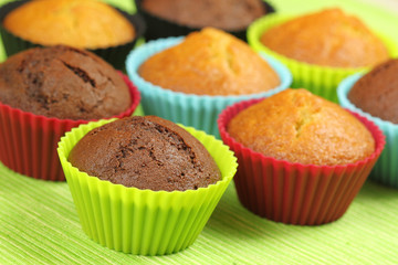 Muffins in colorful silicon moulds on green background