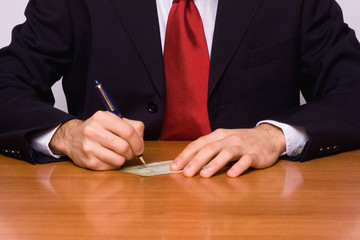 businessman signing a cheque
