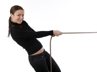 smiling young girl pulling grey rope, tug-of-war.