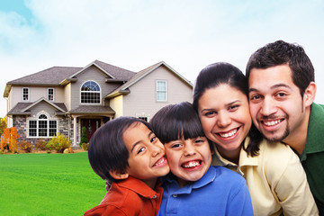 Happy smiling small family in front of house