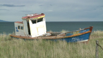 An old abandoned fishing boat beached on the shore