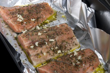 Three steaks of freshly seasoned pink salmon on foil