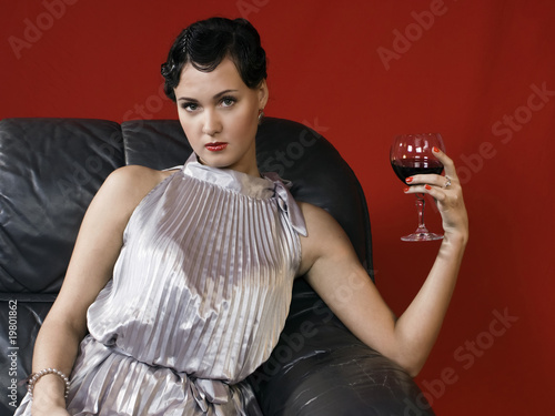 Beautiful young woman with a glass of wine.
