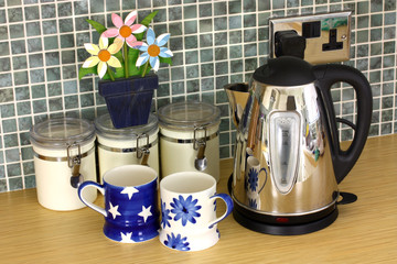 Kitchen counter with kettle and cups and flowers