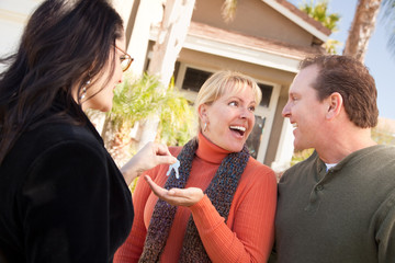Hispanic Female Real Estate Agent Handing Keys to Excited Couple