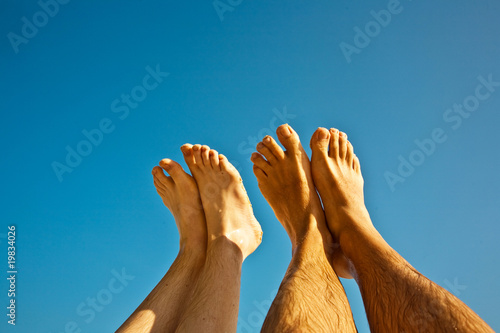 leg and feet of a man and a child in front of the clear blue sky