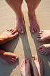 feet of family in the fine sand of the beached in a circle