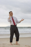 Geschäftsmann telefoniert am Strand