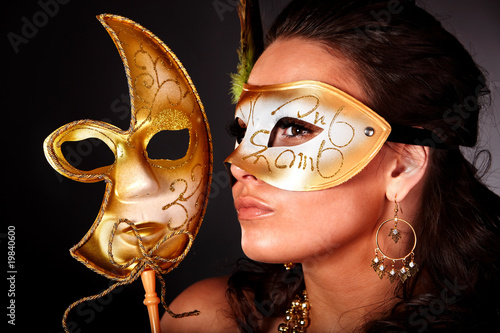 Young woman with gold mask on grey background.