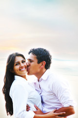 Happy young people hugging and kissing portrait at the beach