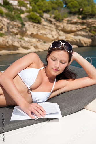 Attractive woman sunbathing on luxury boat