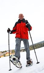 Senior at the snow-shoe walking in winter