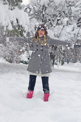 Girl in winter clothing throwing snow in the air