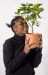 jeune feme souriante tient un oranger en pot contre elle