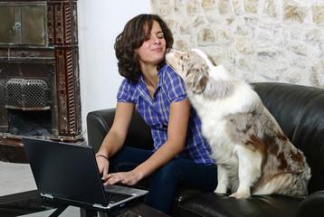 chien donnant un bisou à sa maîtresse devant l'ordinateur