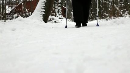 Senior mit Krücken nach Knieoperation, beim Winterspaziergang