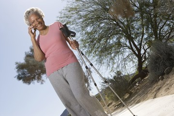 Senior woman stands on phone with walking poles