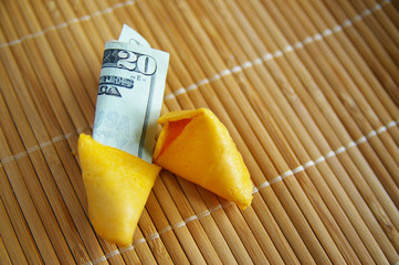broken open fortune cookie, with money inside