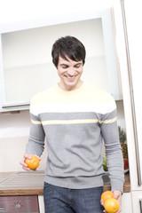 junger mann jongliert mit orangen