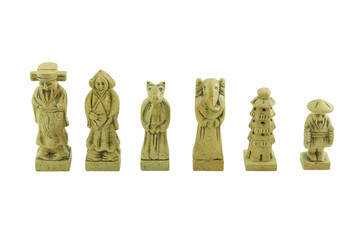 White pieces of a stone chess set isolated on white background