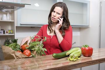 frau beim telefonieren mit gemüse