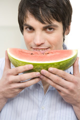 junger mann isst melone