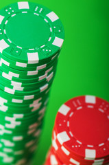Casino chips and cards against green background