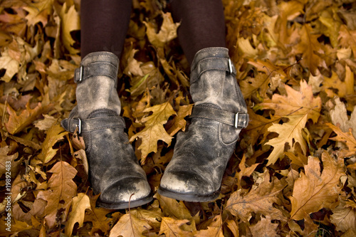 Woman's legs and feet in autumn leaves