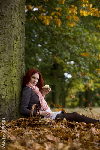 A young woman sitting beneath a tree, eating bread and cheese