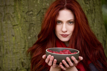 A young woman holding a bowl of raspberries
