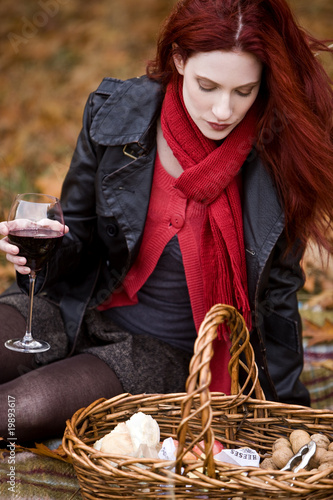 A young woman looking in picnic basket, holding a glass of wine